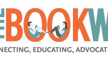 """This is the WNBA's Bookwoman logo. It says The in teal letters and Bookwoman in a mix of orange and teal letters. Two women are reading books in the """"O""""s. Underneath it says, """"Connecting, Educating, Advocating & Leading since 1917."""""""