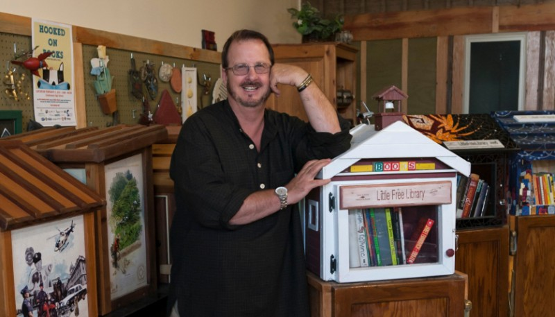 Todd Bol smiles and rests his arm against a Little Free Library.
