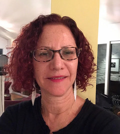 Headshot of Deborah Batterman. She has short curly red hair and wears glasses.
