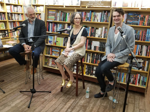 McCann, Batterman, and Lowe sit in front of microphones in front of a bookcase at a panel discussion.