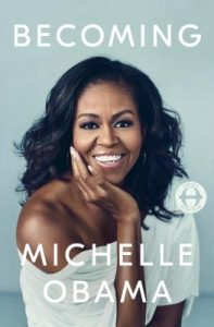 Cover of Becoming has a blue background and a photo of Michelle Obama wearing a white off-the-shoulder top.
