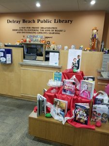 The front desk of the Delray Beach Public Library and a book display of cookbooks and party-planning books.