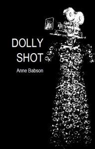 The cover of Dolly Shot has a black background and an abstract dress with a video camera instead of a head above the dress.