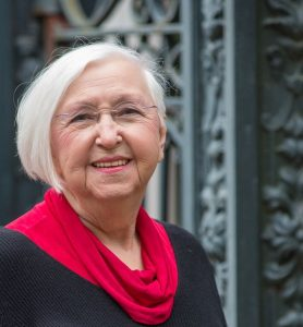 Photo shot of older woman with short white hair. She is wearing a red scarf and a black shirt.