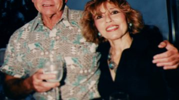 Claudia and Bob Riess pose for a photo. His arm is around her shoulder and they both hold a drink.