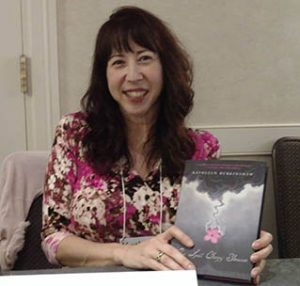 Photo of Kathleen Burkinshaw holding a copy of The Last Cherry Blossom.