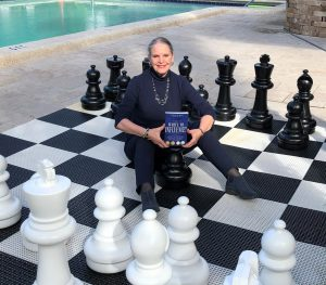 Carla Bass stands in the center of a giant chess set and holds her book, Write to Influence!
