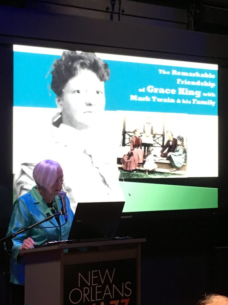 "Miki Pfeffer gives a talk called ""The Remarkable Friendship of Grace King with Mark Twain and Family"" for the Louisiana State Museum. She stands at a podium with a screen behind her."