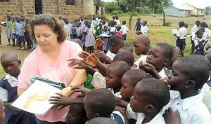 Librarian Isabella Rowan distributes books to children at a school in Kenya.