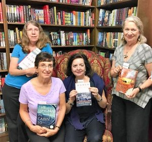 Four women pose in front of a bookshelf holding books.