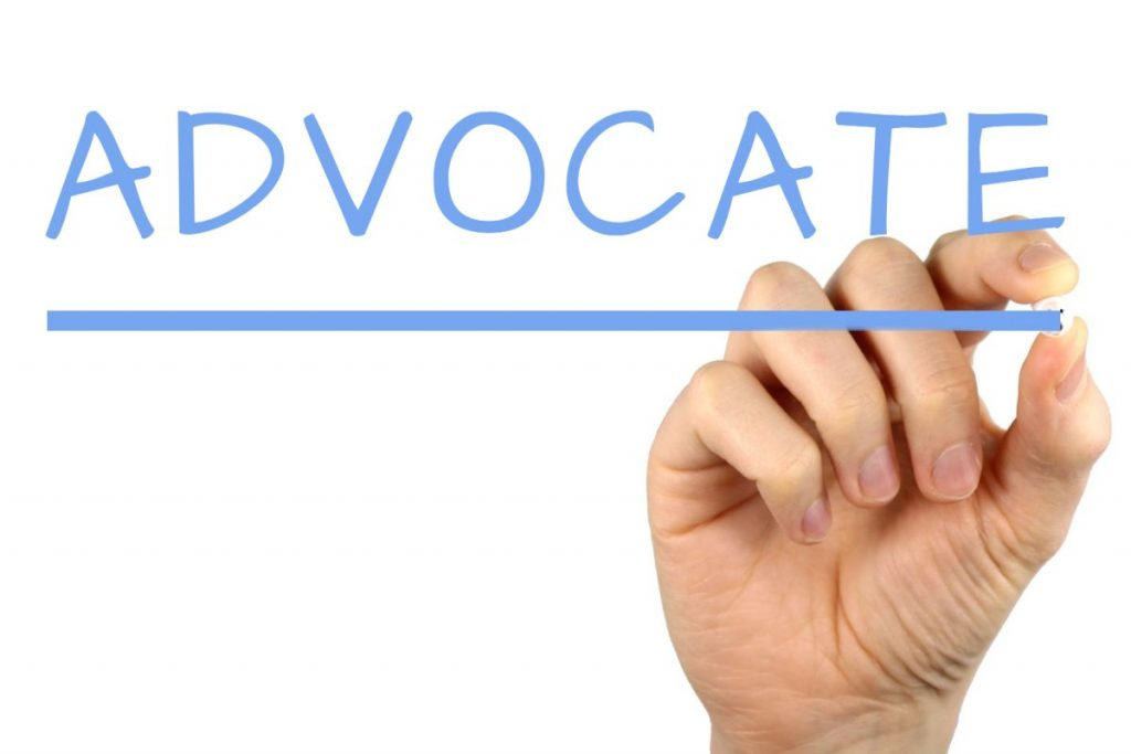 A hand is writing out ADVOCATE.