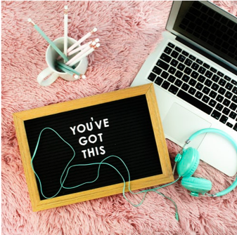 "A silver laptop sits open next to sea green headphones, a mug full of chalk pens, and a small chalkboard that says ""You've Got This."""
