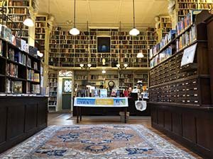 Photo of inside the Providence Athenaeum, which shows lots of books on shelves, an old card catalog, and a table with a National Library Week banner draped over it.