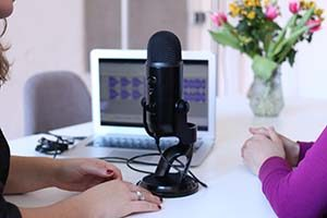 The arms of two women are featured next to a mic and a laptop.
