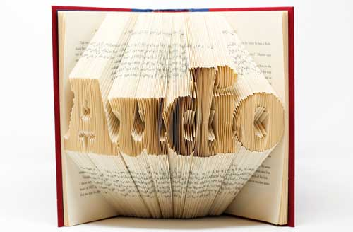 The word audio is folded into the paper edges of a book.