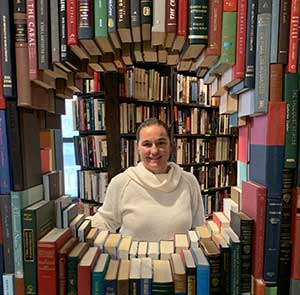 Jennifer Holmes, WNBA National Board member, stands in the center of circular frame made of books