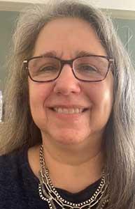 Lisa Leyenda has medium-length hair, wears glasses, and is smiling