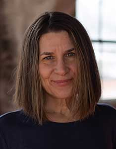 Tess Kelly, 2020 WNBA Writing Contest winner for flash prose, has medium-length straight brown hair and is smiling. She is wearing a dark blue shirt.