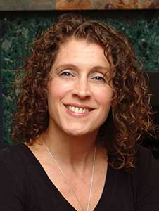 Hannah Mary McKinnon of First Chapter Fun has medium-length, brown, curly hair and is wearing a v-neck black shirt. She is smiling.