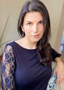Lauren Parvizi has long dark hair, has a half-smile, and is wearing a blue dress with long, lace sleeves.