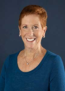 Linda Rosen has cropped, red hair, is wearing an aqua long-sleeved shirt, and is smiling.