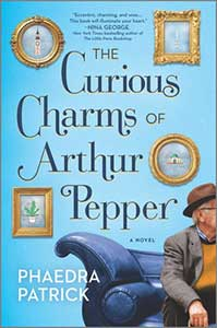 The book cover for The Curious Charms of Arthur Pepper has a sky blue background that looks like a wall. Hanging on the wall are four pictures, each in gilded frames—two round, two rectangles. The bottom right corner shows half of a blue couch. Seated on the couch is an older man whose left half of his body is cut off by the edge of the book.