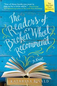 Wood boards that are painted bright blue serve as the background for the book cover for The Readers of Broken Wheel Recommend. There is a stack of books on the bottom of the cover with the top one's pages fanned open.