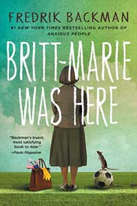 A sky that is shades of green, white, and blue-green covers most of the book cover for Britt-Marie was Here. The sky touches the ground which is green grass. In the middle, standing on the grass, is a woman, her back to us. She is wearing a brown blazer and a below-knee-length brown skirt. On the grass to her left is a large purse with items falling out. On her right is a soccer ball with a rodent standing upright on it.