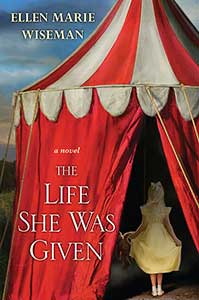 There is a big red circus tent with a red and white striped roof on the cover of The Life She was Given. In the tent opening is the back of a young girl with pale, blonde hair wearing a yellow dress.