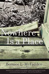 The book cover for Nowhere Is a Place is in black and white and shows wood boards abutting the corner of a building with one board curling up. Bushes show in the background.