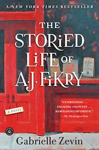 The book cover for the Storied Life of AJ Fikry shows the front door and window of a bookstore. In the window are books on display. The front door is bright red and has a sign hanging from the door that says A Novel.