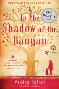 The book cover for In The Shadow of the Banyan uses shades of tan to show a tree with branches and leaves and red to show the ground, birds flying around the trees, and a mother and a young daughter.
