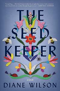 The book cover for the Seed Keeper, a 2021 Great Group Reads selection, is bluish-purple. Throughout the title, embroidered flowers and bees are woven.